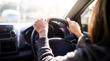 Female hands on the steering wheel of a car while driving. sunset the background, the windshield and road
